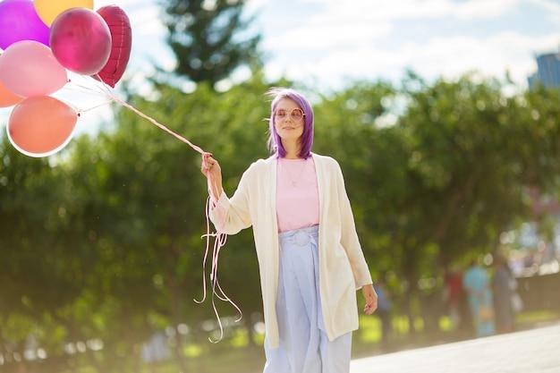 Junge dame mit dem purpurroten haar in den rosa gläsern mit den ballonen, die draußen stehen