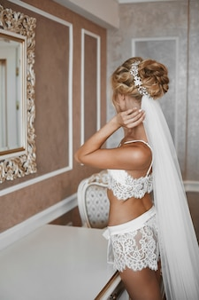 Junge dame mit dem schlanken körper in den weißen spitzenwäsche, die ihr spiegelbild im spiegel im weinleseinnenraum betrachten. junge blonde frau, die ihre hochzeitsfrisur anpasst. morgenvorbereitung der jungen braut