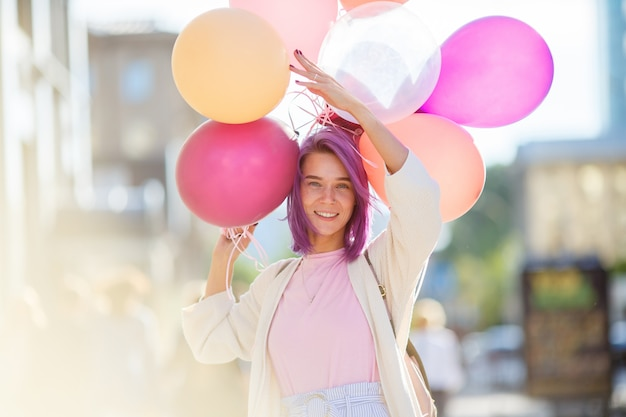 Junge dame mit dem violetten haar, das in der stadtstraße mit bündel baloons steht