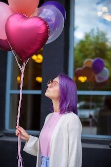 Junge dame mit dem violetten haar in den rosa schauspielen mit den luftballonen, die oben schauen