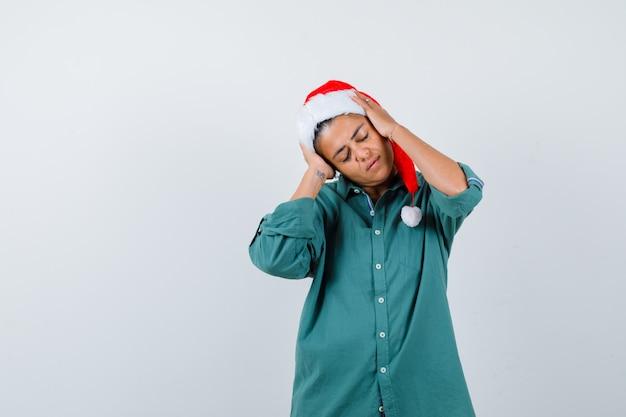 Junge dame mit den händen auf dem kopf in weihnachtsmütze, hemd und entspanntem blick, vorderansicht.