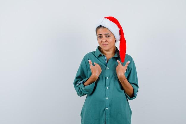 Junge dame mit den händen auf der brust in weihnachtsmütze, hemd und vorsichtigem blick, vorderansicht.