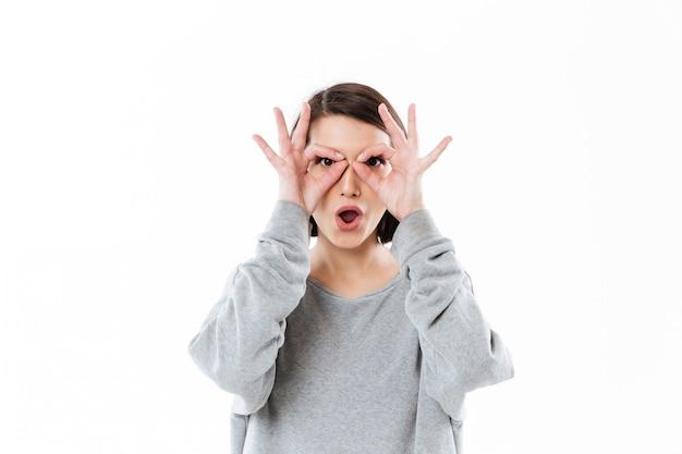 Junge dame mit den händen vors gesicht wie eine brille