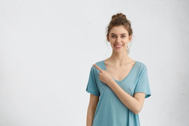 Junge dame mit dunklem haar, blauen augen und fröhlichem ausdruck, der mit finger auf kopierraum zeigt