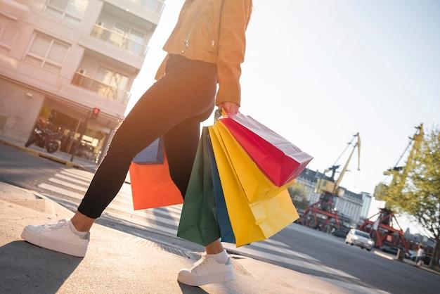 Junge dame mit einkaufstaschen auf straße