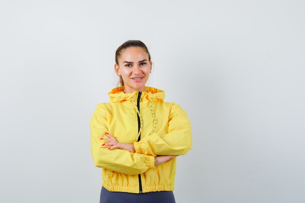 Junge dame mit gekreuzten händen in gelber jacke und zufriedenem blick. vorderansicht.