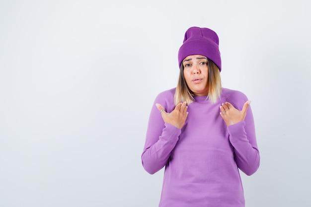 Junge dame mit händen auf der brust in lila pullover, mütze und ängstlich aussehend. vorderansicht.