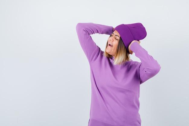 Junge dame mit händen hinter dem kopf in lila pullover, mütze und glücklich aussehend. vorderansicht.