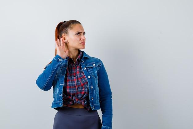 Junge dame mit hand hinter dem ohr in kariertem hemd, jeansjacke und vorsichtigem blick. vorderansicht.
