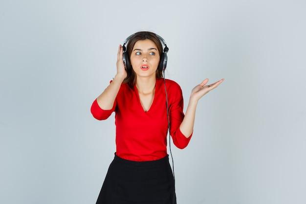 Junge dame mit kopfhörern, die musik hören, während sie etwas in der roten bluse zeigen
