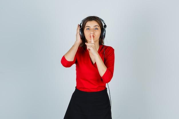 Junge dame mit kopfhörern, die musik hören, während sie stille geste in der roten bluse zeigen