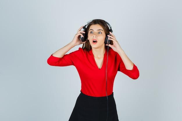 Junge dame mit kopfhörern, die weg in der roten bluse, im rock schauen und verwirrt schauen