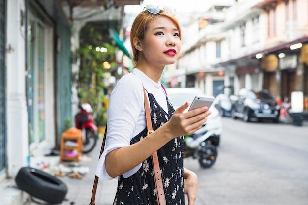 Junge dame mit smartphone auf straße