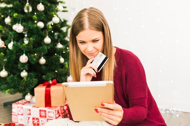 Junge dame mit tablette und plastikkarte nahe geschenkboxen und weihnachtsbaum