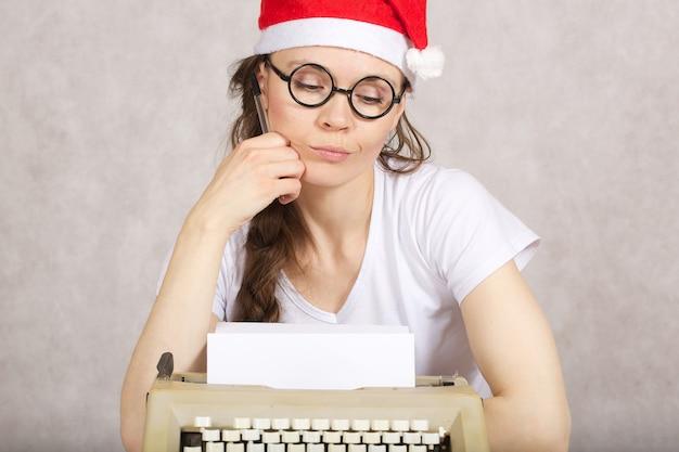 Junge dame mit weihnachtsmann-hut in der nähe der schreibmaschine.