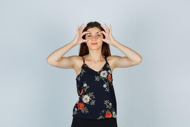 Junge dame öffnet augen mit fingern in bluse, rock und sieht lustig aus. vorderansicht.