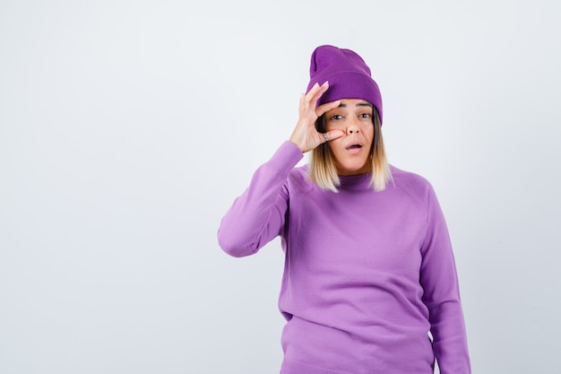 Junge dame öffnet das auge mit dem finger in lila pullover, mütze und sieht verwirrt aus, vorderansicht.