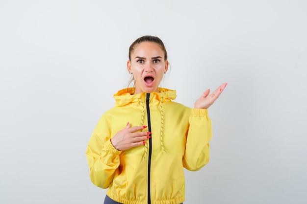 Junge dame posiert in gelber jacke und schaut verwirrt, vorderansicht.