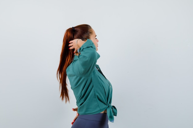 Junge dame posiert mit kopf hinter dem kopf im grünen hemd und sieht charmant aus.