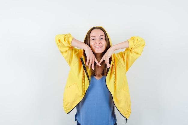 Junge dame posiert, während sie die ellbogen in t-shirt, jacke streckt und entspannt aussieht. vorderansicht.