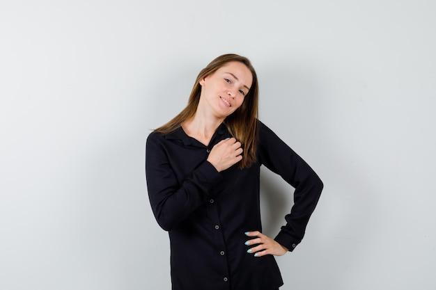 Junge dame posiert, während sie die hand auf der brust hält