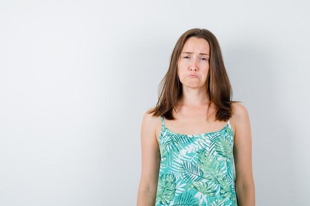 Junge dame posiert, während sie in bluse steht und beleidigt aussieht. vorderansicht.