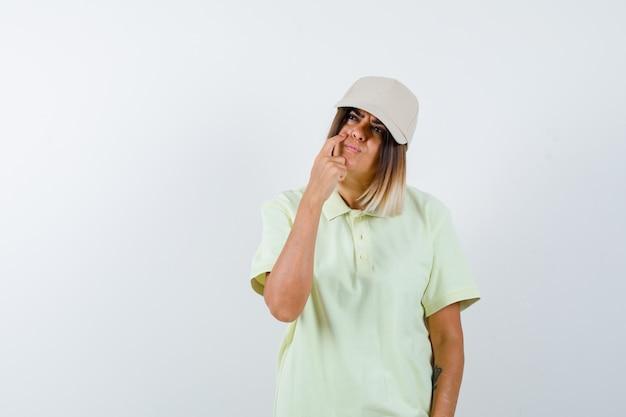 Junge dame schaut auf, während sie in t-shirt, mütze denkt und nachdenklich aussieht. vorderansicht.