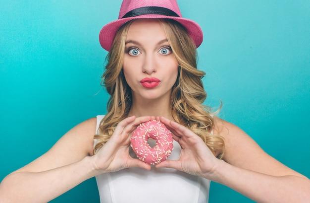 Junge dame schaut vor der kamera und hält einen donut mit rosa glasur darüber
