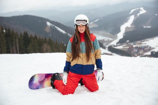 Junge dame snowboarder sitzt auf den pisten frostigen wintertag