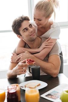 Junge dame umarmt ihren mann, während sie frühstücken