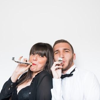 Junge Dame und Mann in Abendgarderobe mit Partyflöten