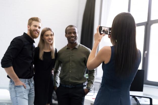Junge dame und zwei junge männer lassen sich fotografieren