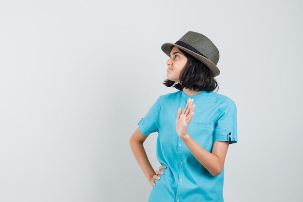 Junge dame winkt hand zum abschied im blauen hemd, hut