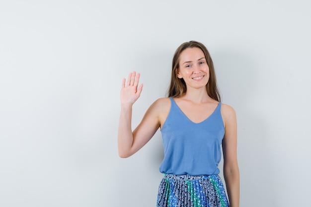 Junge dame winkt hand zum abschied in blauer bluse, rock und sieht froh aus. vorderansicht.