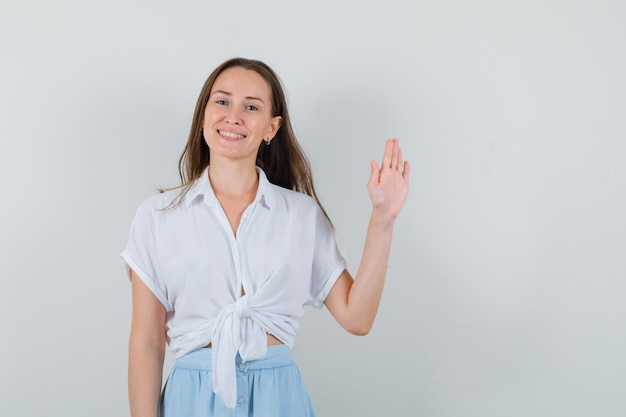 Junge dame winkt hand zum abschied in bluse und rock und sieht froh aus