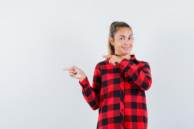 Junge dame zeigt auf die linke seite im karierten hemd und sieht fröhlich aus