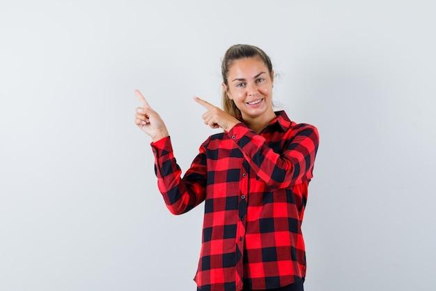 Junge dame zeigt auf die obere linke ecke im karierten hemd und sieht fröhlich aus