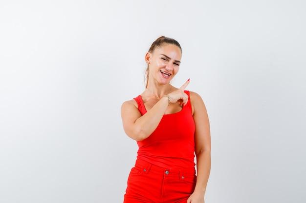 Junge dame zeigt auf die obere rechte ecke im roten unterhemd, in der roten hose und sieht fröhlich aus. vorderansicht.