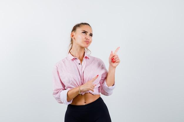 Junge dame zeigt auf die obere rechte ecke in hemd, hose und sieht nachdenklich aus