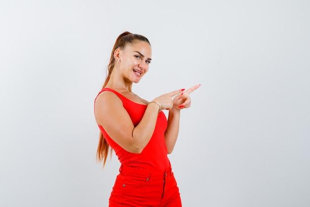 Junge dame zeigt auf die rechte seite in rotem unterhemd, roter hose und sieht fröhlich aus. vorderansicht.