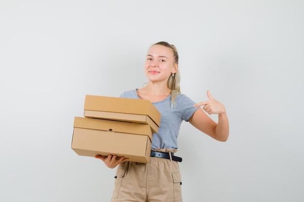 Junge dame zeigt auf pappkartons in t-shirt und hose und sieht fröhlich aus