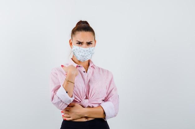 Junge dame zeigt auf sich selbst in hemd, maske und sieht wütend aus. vorderansicht.