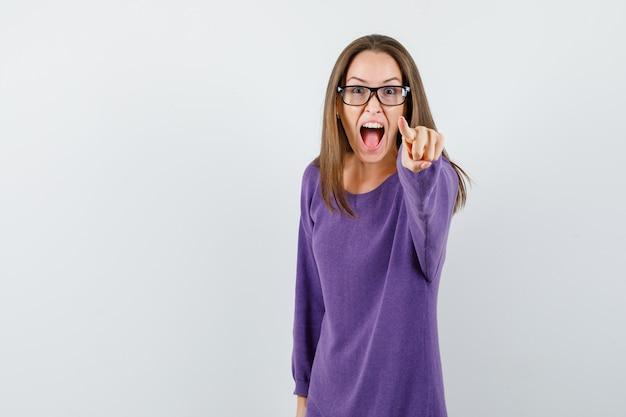 Junge dame zeigt auf sie im violetten hemd und sieht wütend aus. vorderansicht.