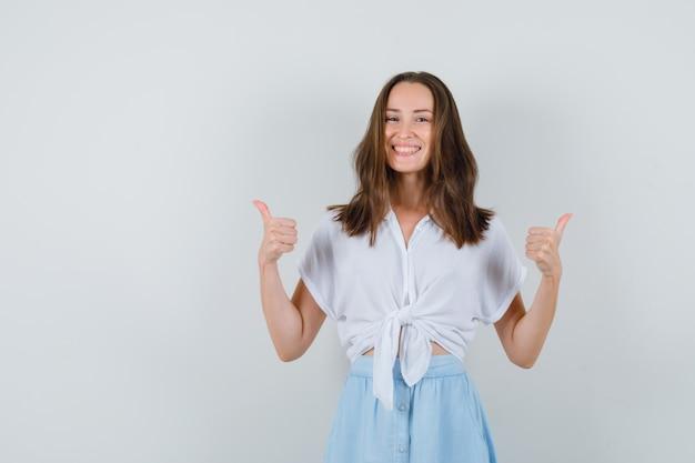 Junge dame zeigt daumen hoch in bluse und rock und sieht fröhlich aus