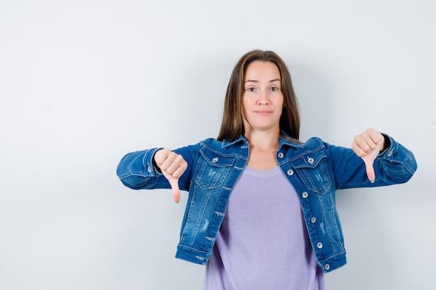 Junge dame zeigt doppelte daumen nach unten in t-shirt, jacke und sieht selbstbewusst aus. vorderansicht.