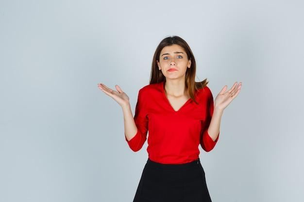 Junge dame zeigt hilflose geste in roter bluse, rock und hoffnungslos aussehend