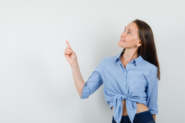Junge dame zeigt in blauem hemd, hose und sieht fröhlich aus