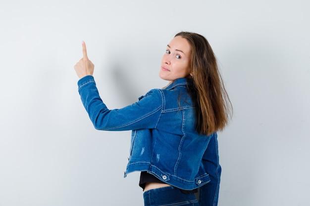 Junge dame zeigt in bluse, jacke und sieht selbstbewusst aus, rückansicht.