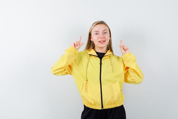 Junge dame zeigt in gelber jacke, hose und sieht fröhlich aus. vorderansicht.