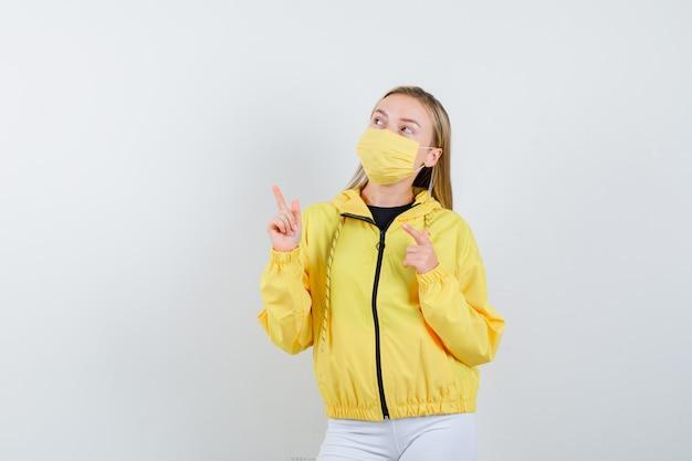 Junge dame zeigt in jacke, maske und hoffnungsvoll, vorderansicht.